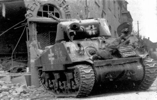 An American built M4A3 (76) Sherman medium tank, captured and pressed into service by the German army. German markings and the words Beute Panzer (captured tank) were added to the tank to avoid friendly fire. The tank was knocked out by a US M36 Jackson tank destroyer. A dead crew member lies on the front of the tank, believed to have been hit by machinegun fire while attempting to bail out of the stricken tank. Aschaffenburg, Germany. 1945.
