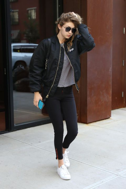 """Hadid rocks her go-to athleisure look with a personalized black bomber jacket featuring a small """"Gigi"""" logo on the chest"""