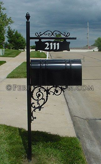 An Ornamental Iron Mailbox Post With Cast Iron Brackets For