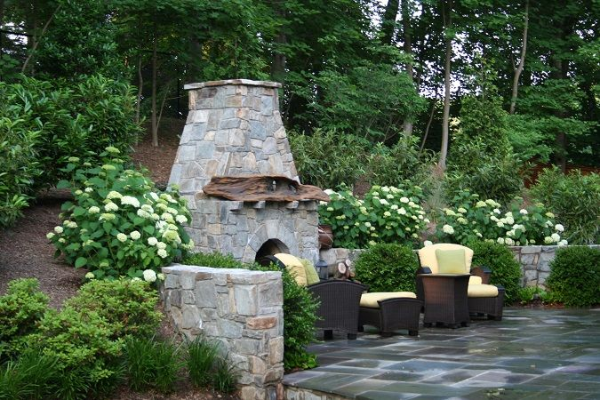 The Sloped Landscape Around This Fieldstone Patio And Fireplace Includes Laurels Hydrangea And