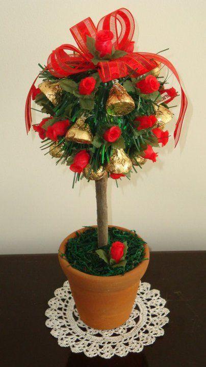 Arbolito con chocolates kisses dorados y flores rojas.