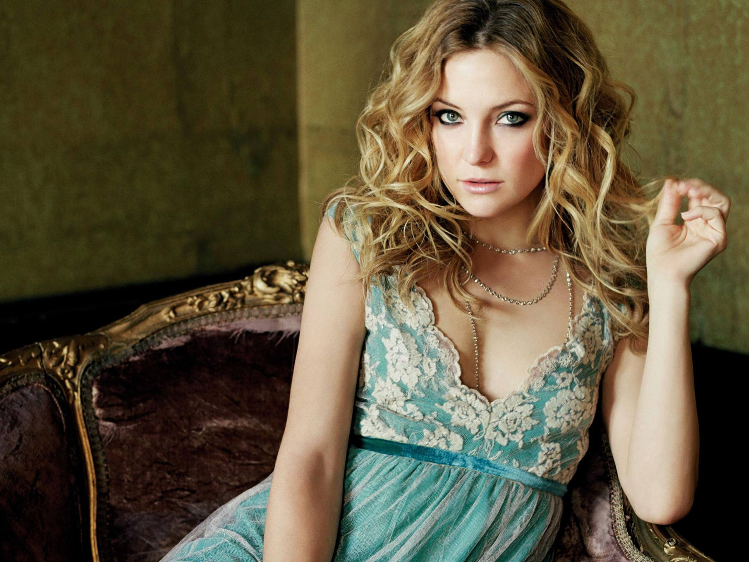 Kate Hudson sitting on a couch in blue dress