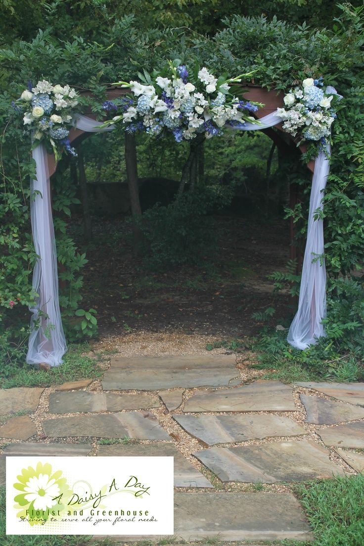 Decorating A Trellis For A Wedding Arbor Decoration With Blue And White Flowers And Tulle Draping