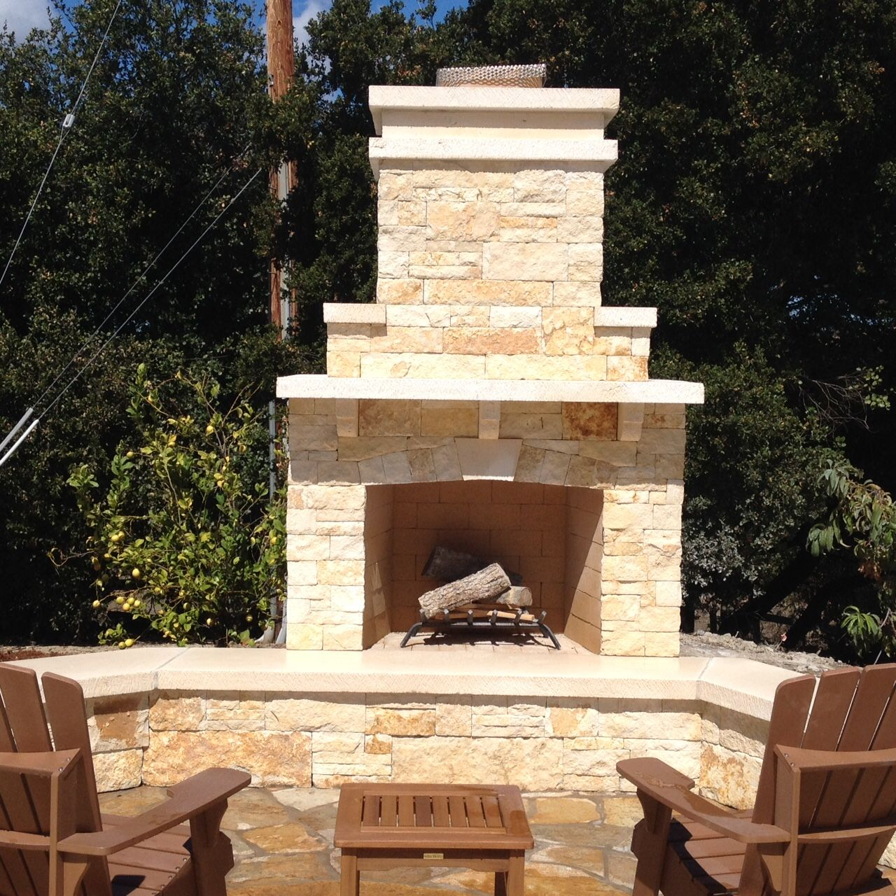 Custom designed outdoor fireplace with seated area, stone mantel and storage.