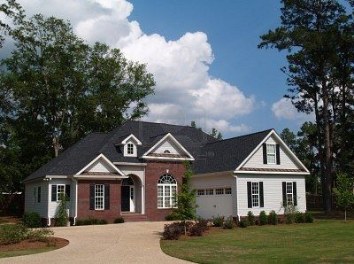 Two Story Residential Home With Brick And Board Siding On The