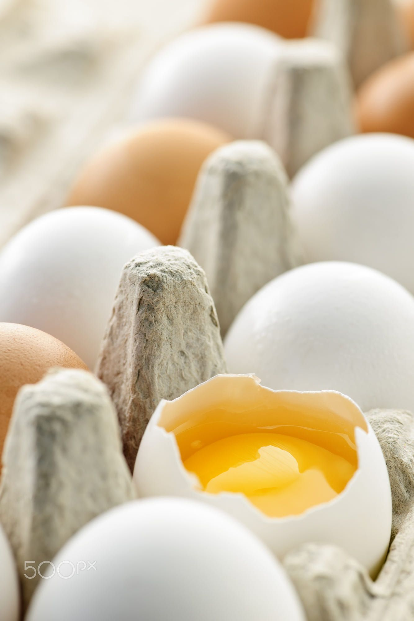 White and brown eggs in carton with broken egg Can dogs