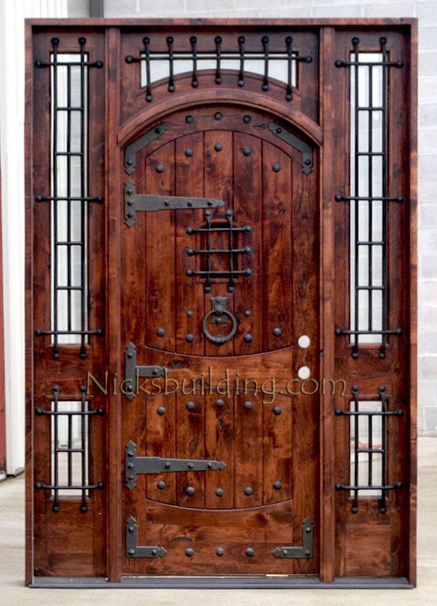 Rustic Exterior Arched Door With Wrought Iron Grills Strap Hinges Clavos Nails And Door
