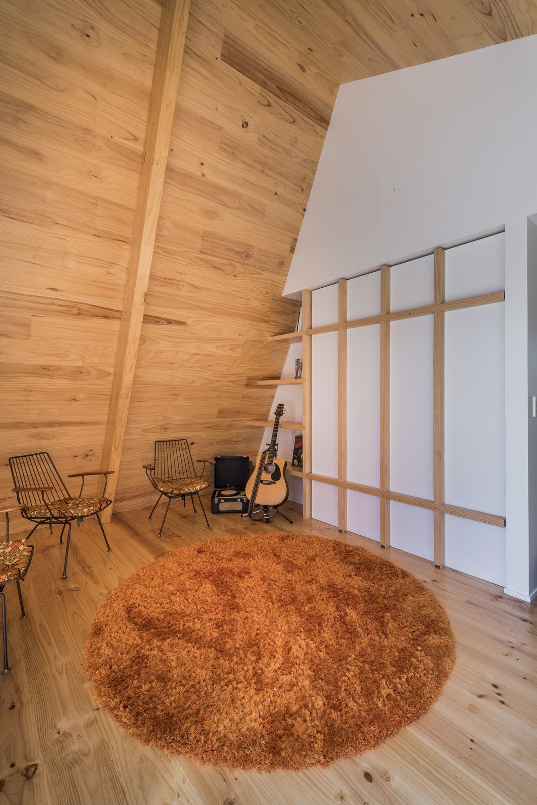 Living room chair light hardwood floor rug floor and shelves cymon his wife angela and their two teenage daughters furnished the home with objects