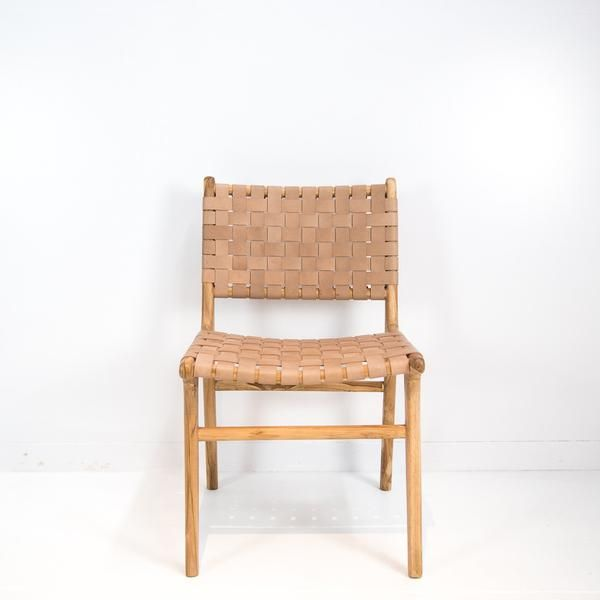 A Teak wood frame forms the base of this chair, finished to reveal the natural grain of the wood. Leather in a soft tan shade is expertly weaved and secured aro