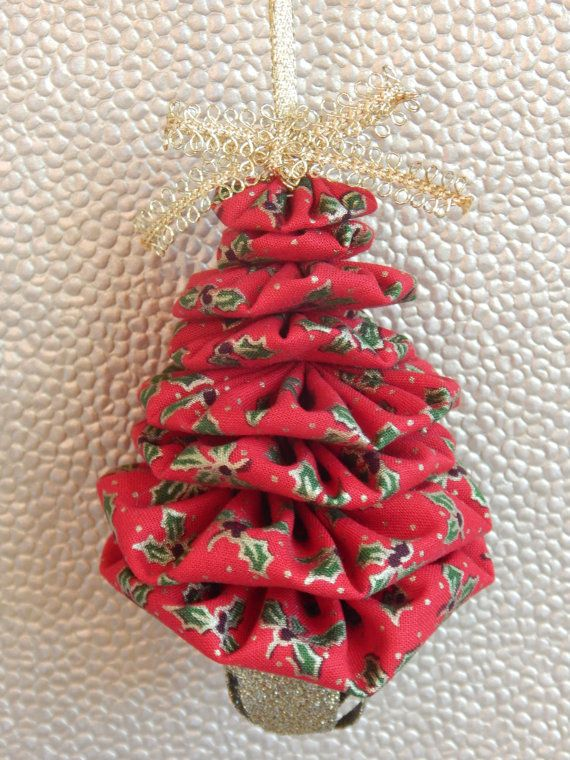 This is a lovely Christmas tree shaped ornament made from yo yos (fabric rounds) in a gold outlined holly print on red. Tree is topped with a gold bow and a glittery gold jingle bell takes the place of a tree trunk. These ornaments are really gorgeous hanging on a Christmas tree surrounded by twinkling lights.  From the top of the tree to the bottom of the bell, ornament measures approximately 4 1/2 and is about 3 at its widest point. Hanger is approximately 3.  This is an original design by…