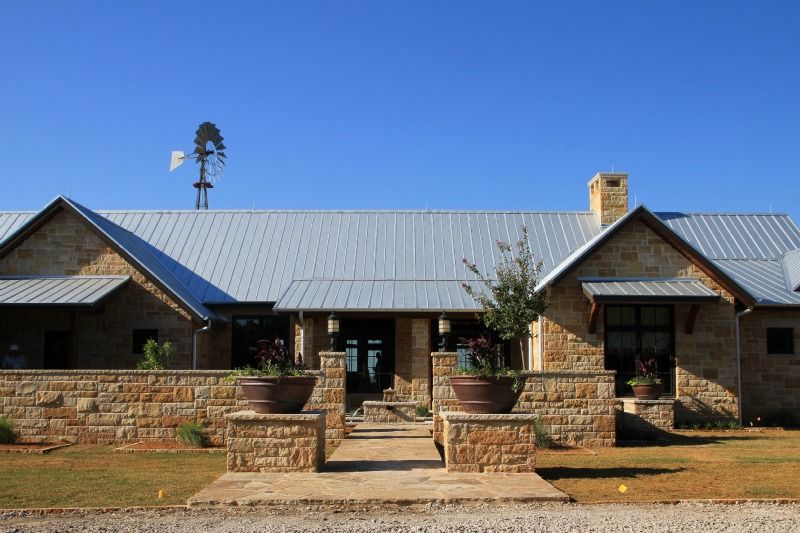 Limestone exterior with standing seam metal roof at a for Roof designs for ranch homes