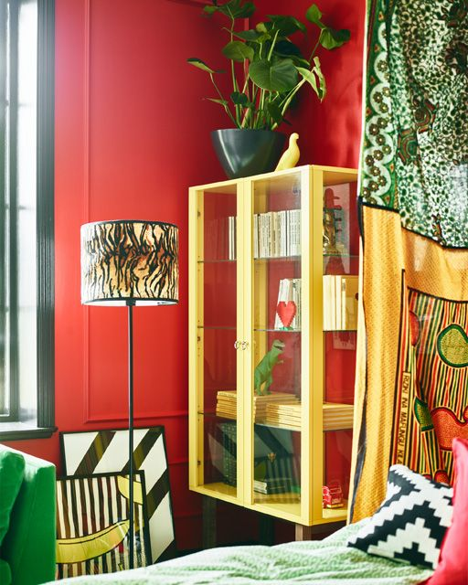 Bright coloured furniture and red walls help make this stylist's dream bedroom.