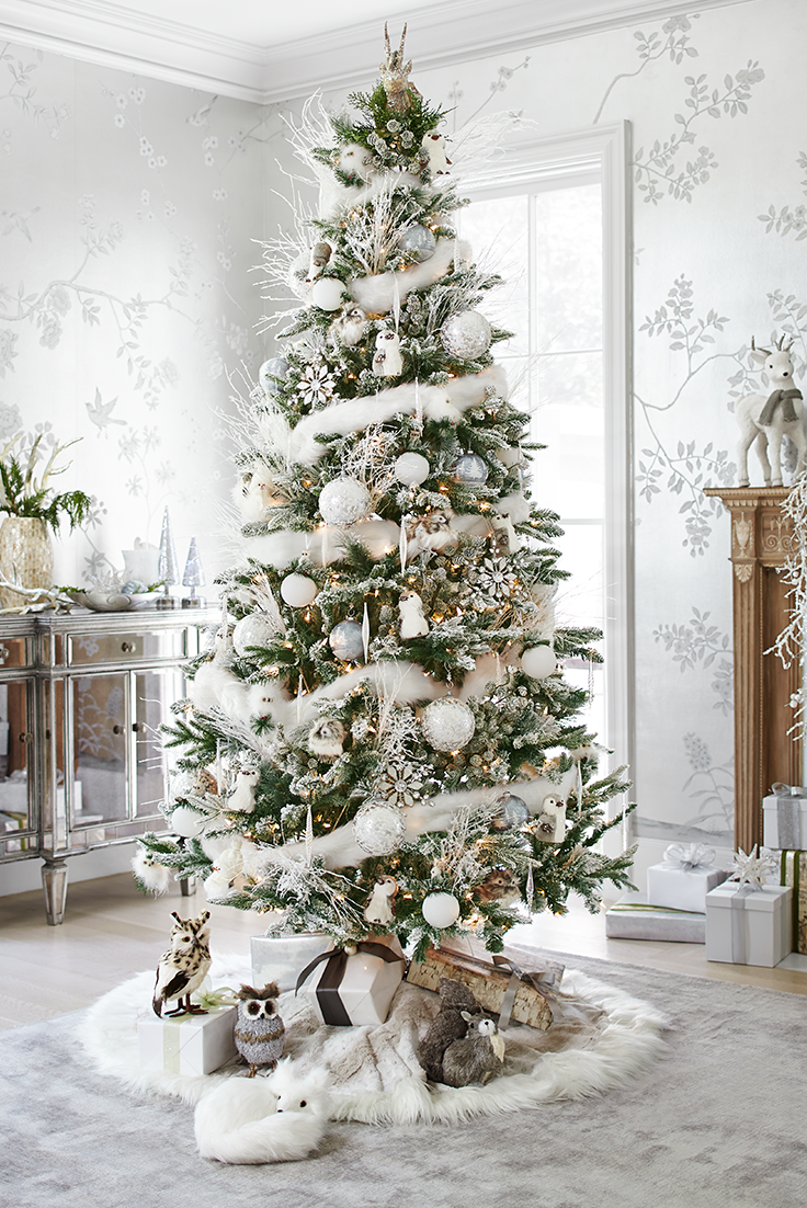 an indoor winter wonderland awaits you with pier 1s frosted noel christmas tree branches sparkle with a touch of frost a reindeer tree topper provides a