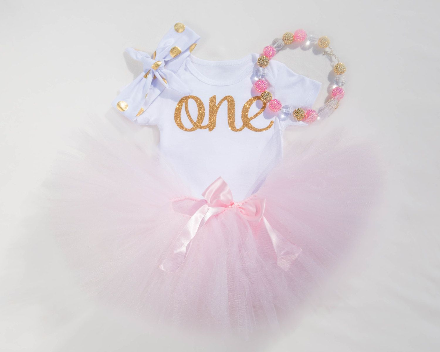 This beautiful outfit is the perfect attire for your little girl's first birthday ! The soft pink tutu and Gold accents really bring out the sweetness of being a girl! This first birthday outfit is even prettier in person!  This outfit is part of our ONE™ collection!!