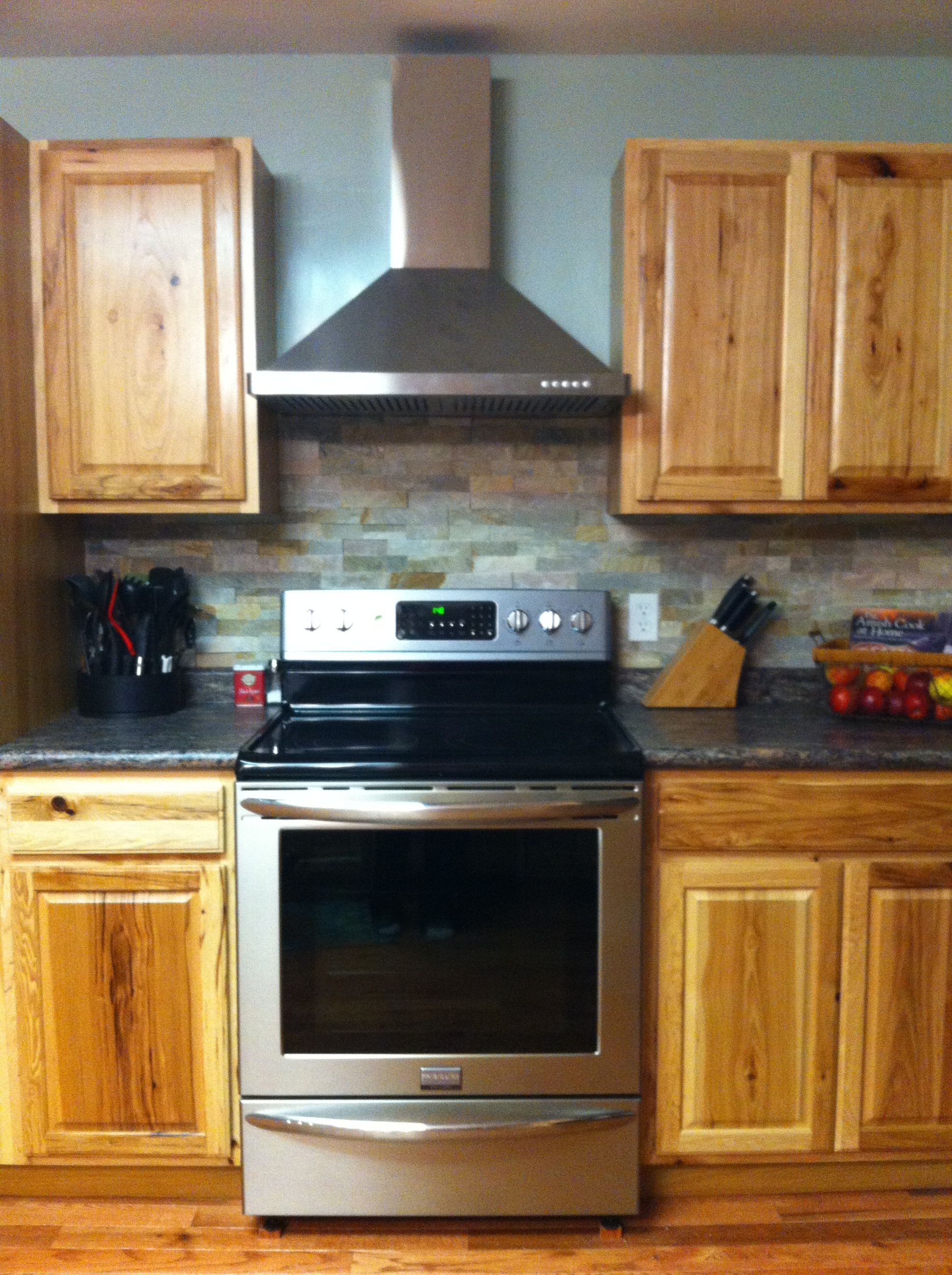 - Stacked Stone Backsplash With Hickory Cabinets And Stainless Range