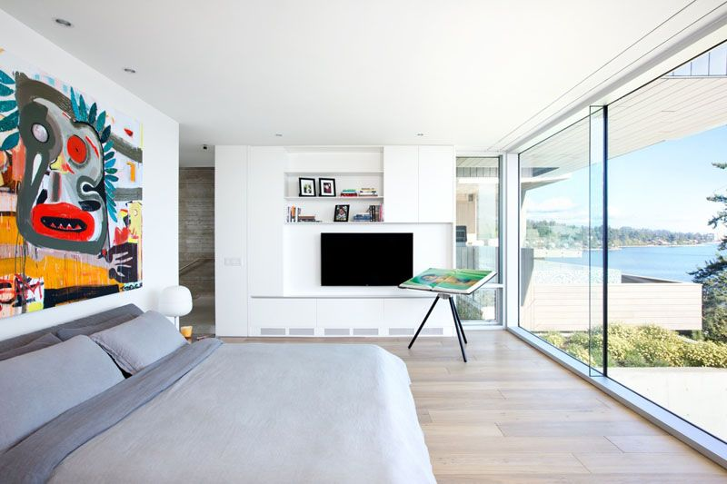 This modern bedroom has large floor-to-ceiling windows, wide plank oak flooring and built-in shelving. A large painting above the bed adds a pop-of-color to the mostly-white room.