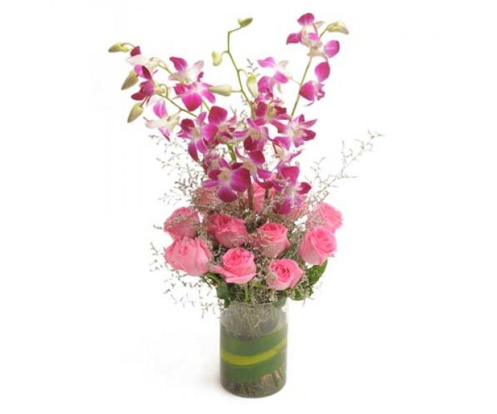 Glass vase arrangement of 12 Pink Roses with 3 purple orchids.