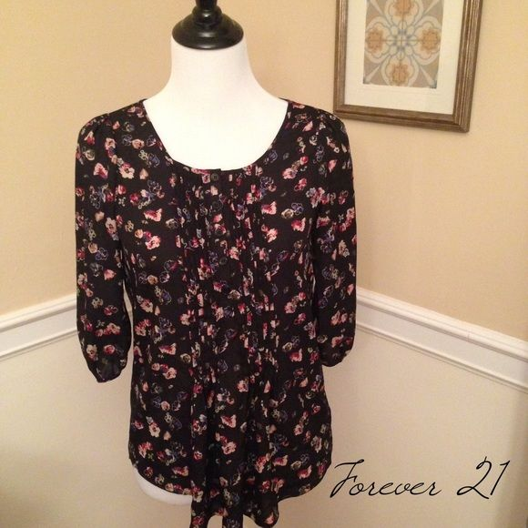 FOREVER 21 Floral Top Make this pretty floral blouse with 3/4 sleeves from FOREVER 21 yours today! Gentle scoop next with buttons from top of neck to halfway down the shirt. Pin tuck pleating on either side of the buttons. Gently worn just a couple of times. 100% polyester.  Forever 21 Tops Blouses
