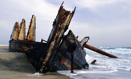 An old wooden hull of a shipwreck on a sandy shore. Photograph: Pete Leonard/zefa/Corbis