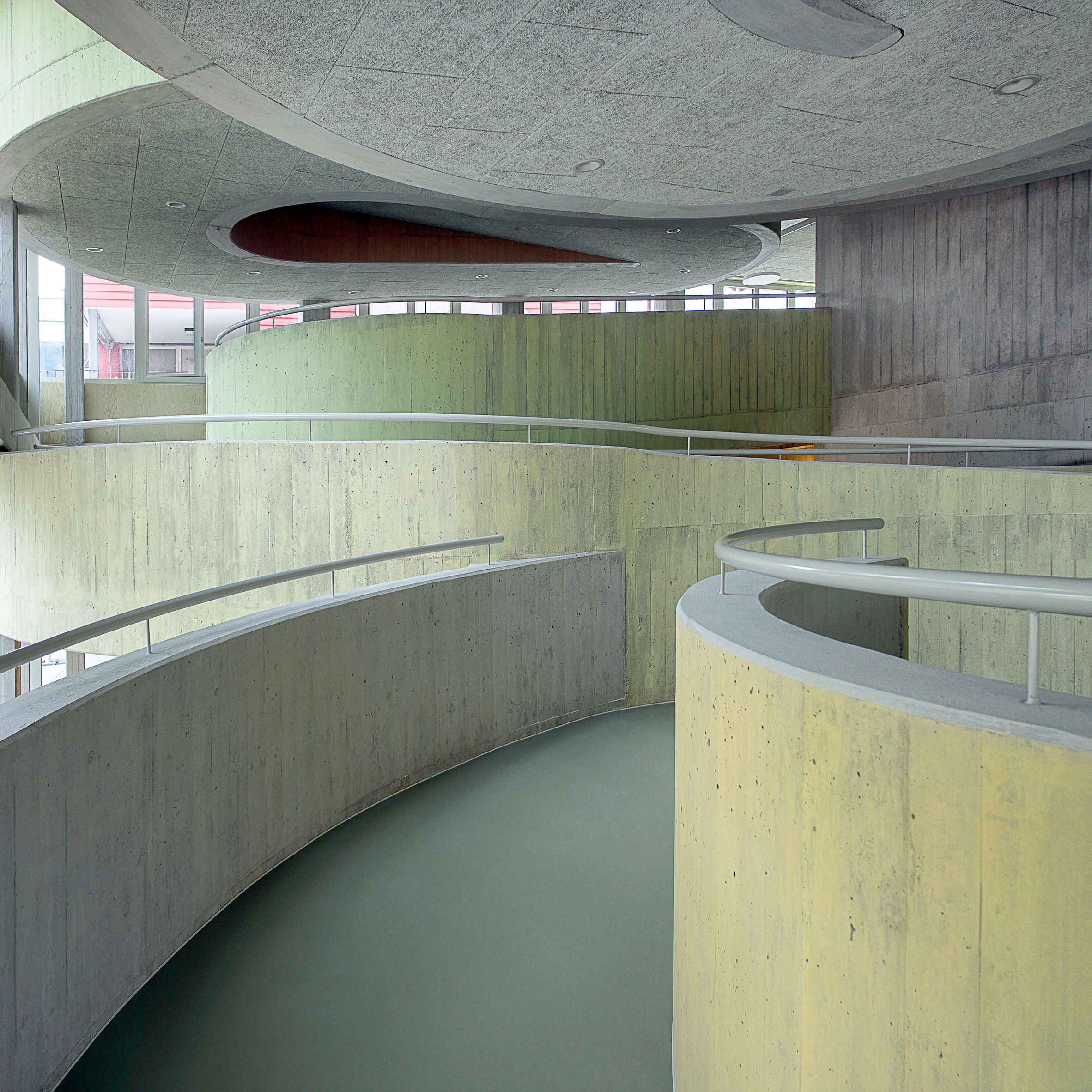 This extension to a day-care centre for disabled adults in the Swiss town of Stans has been kitted out with muted red awnings and spiralling pastel-tinged walkways. Local studio Architekten CM was tasked with designing the building for the Weidli Stans Foundation, which provides accommodation and learning support for adults with multiple physical and mental