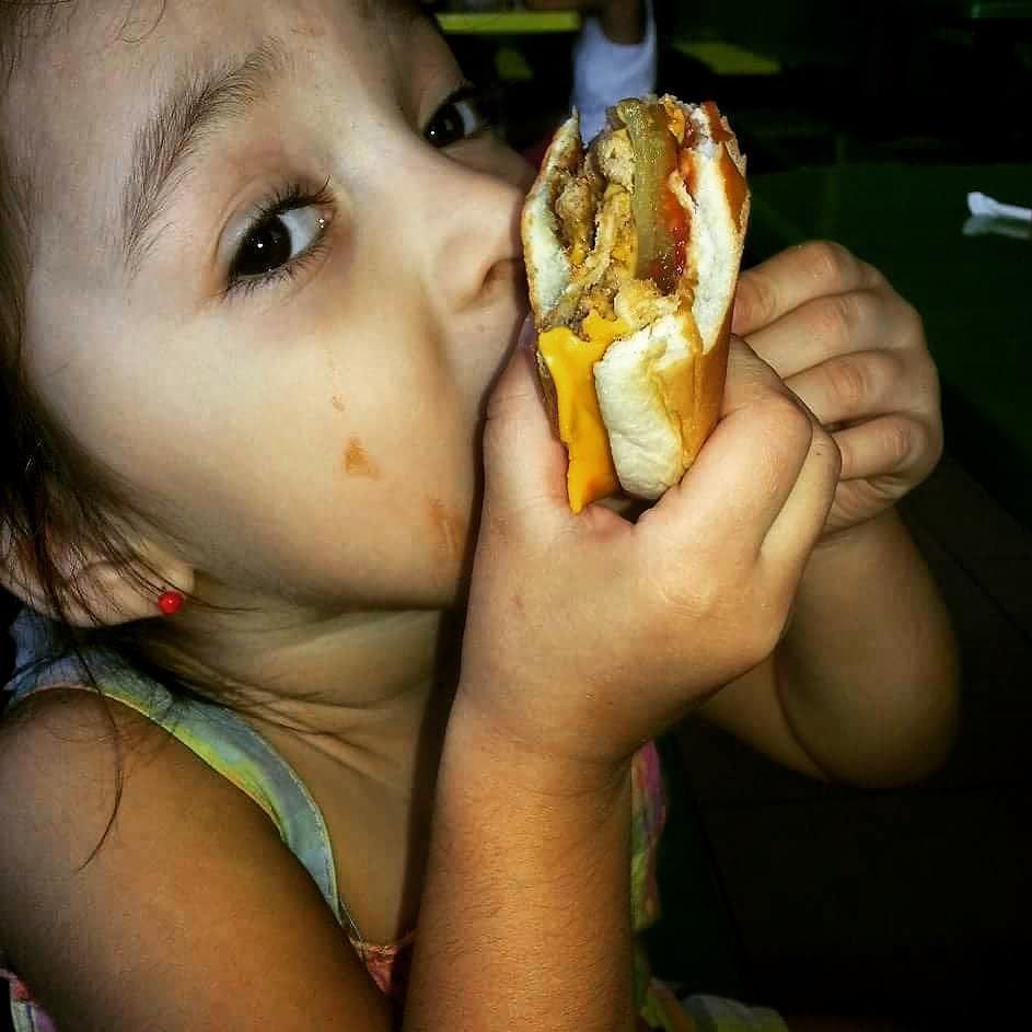 Ella si sabe comer hamburguesas.