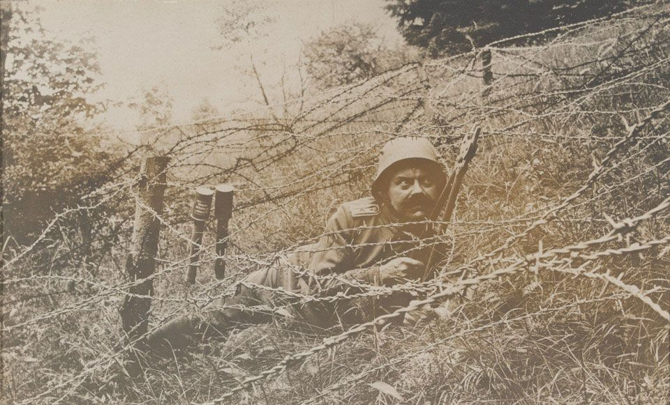A German storm trooper cutting through barbed wire defences during training, 1918.