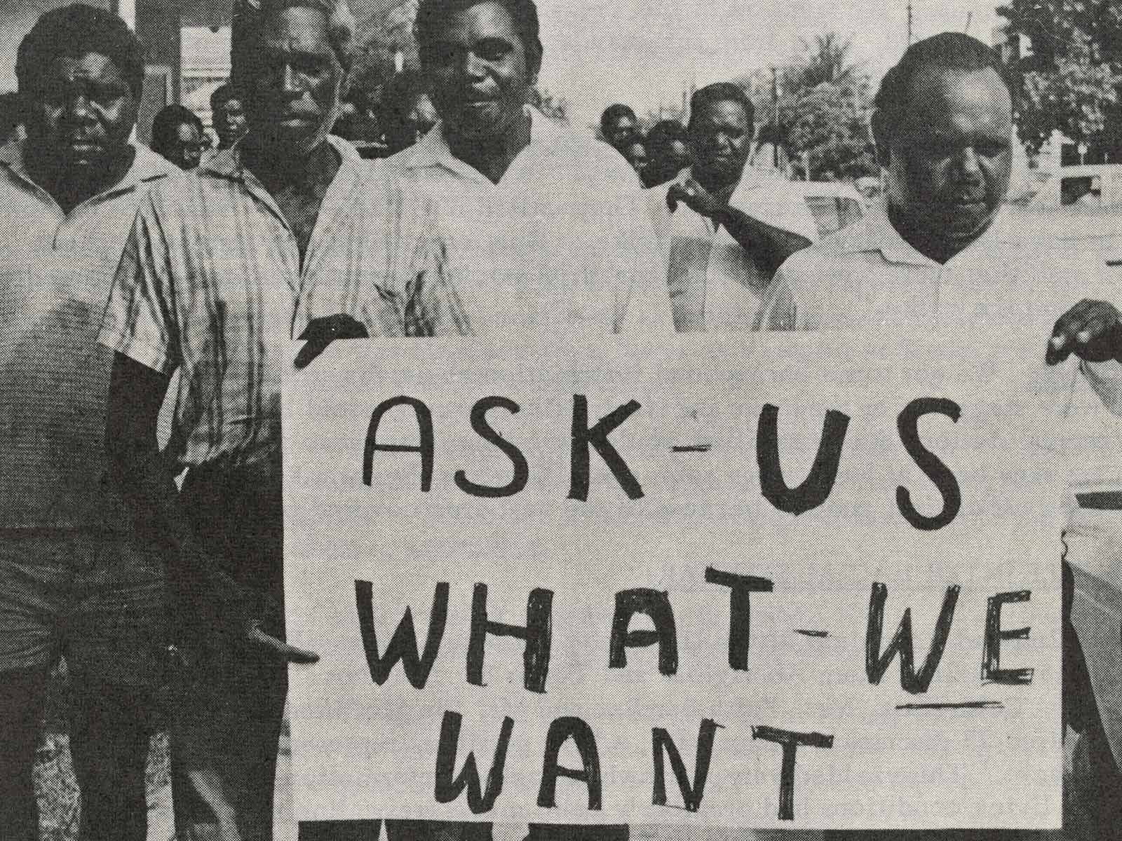 An archival clipping of a newsletter article depicting Aboriginal men walking with a placard that says 'ask us what we want'