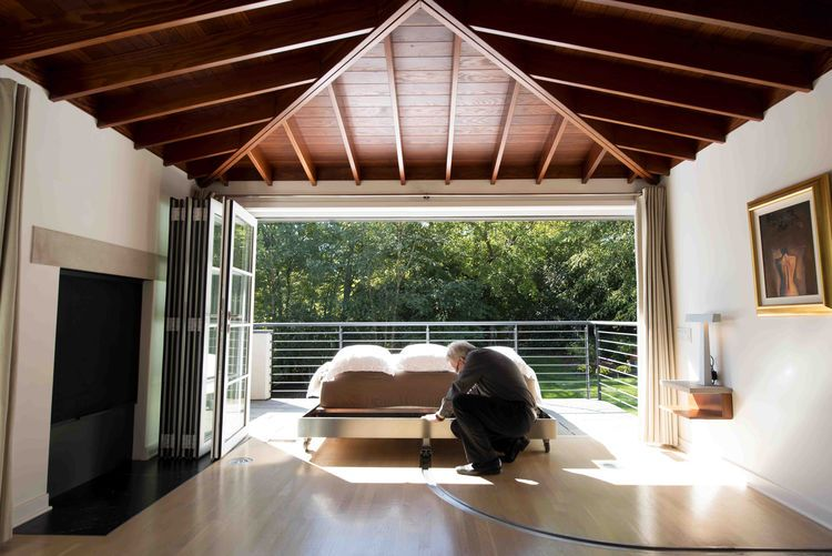 Indoor-outdoor bedroom with movable bed, cedar rafters.