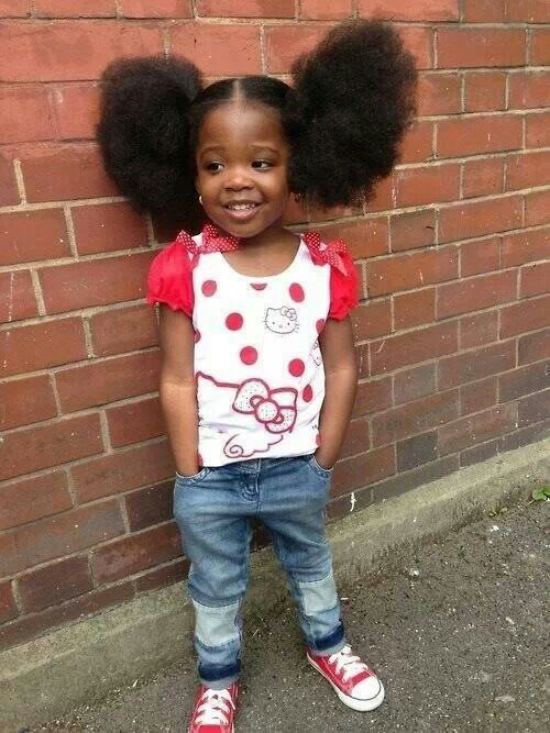 Adorably cute little black girl. Big Afro natural curly puffs ponytails hair. Pretty red hello kitty shirt and blue jeans. Sweetheart!