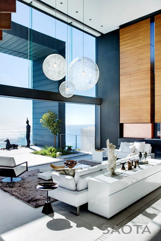 A living room in a luxury home overlooking the ocean sporting an