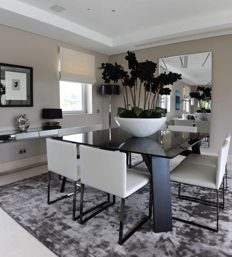 schwarzer Esstisch, weiße Polsterstühle und übergroße Schüssel mit - esszimmer ideen modern