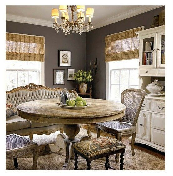 Eclectic Dining table and settee and chairs with charcoal walls and bamboo or matchstick blinds.