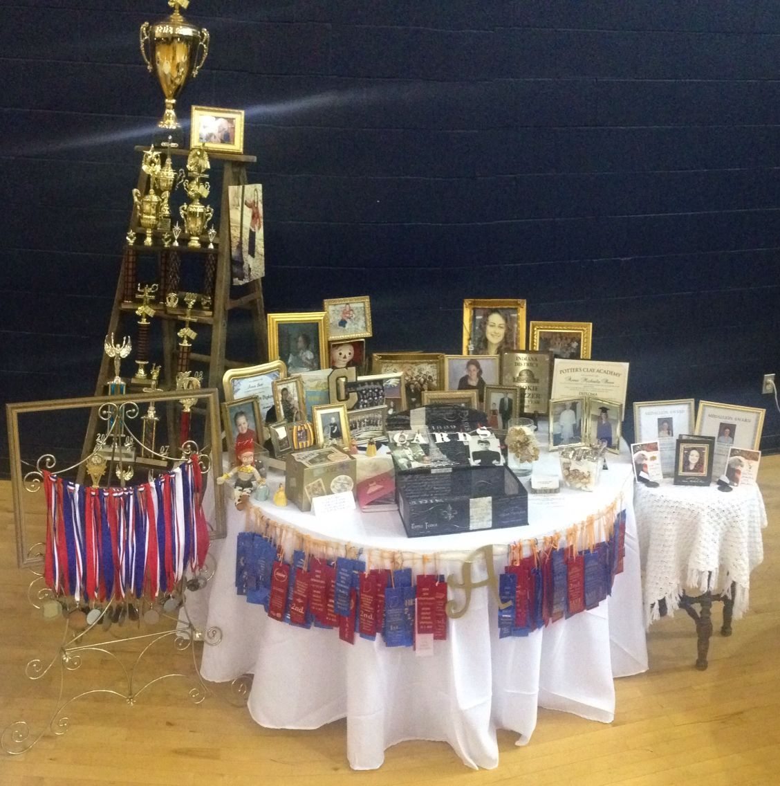 Graduation table with trophies medals and ribbons