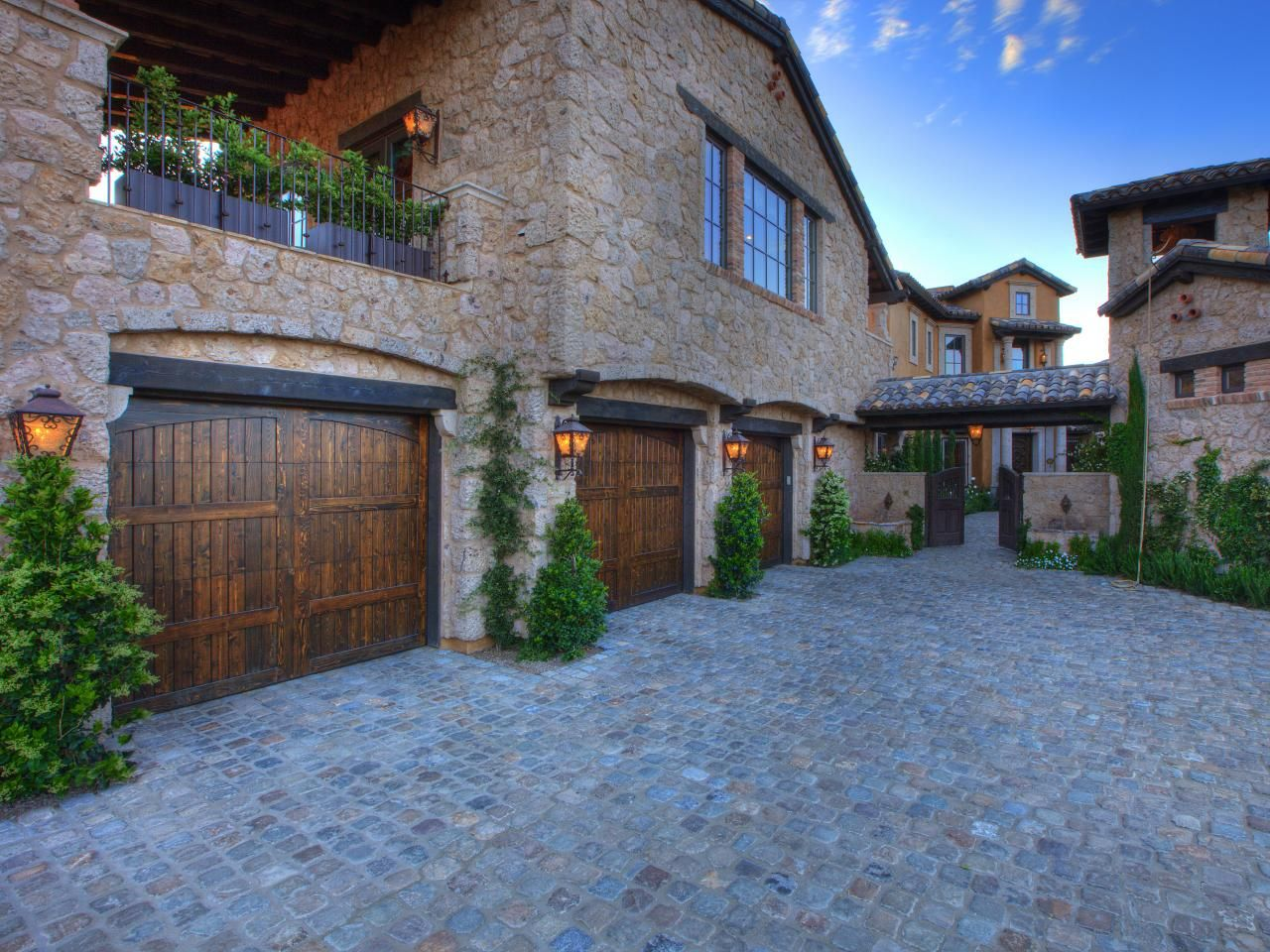 This Motor Court Set Up With Its Stone Surface And Wood Garage Doors Is A  Car