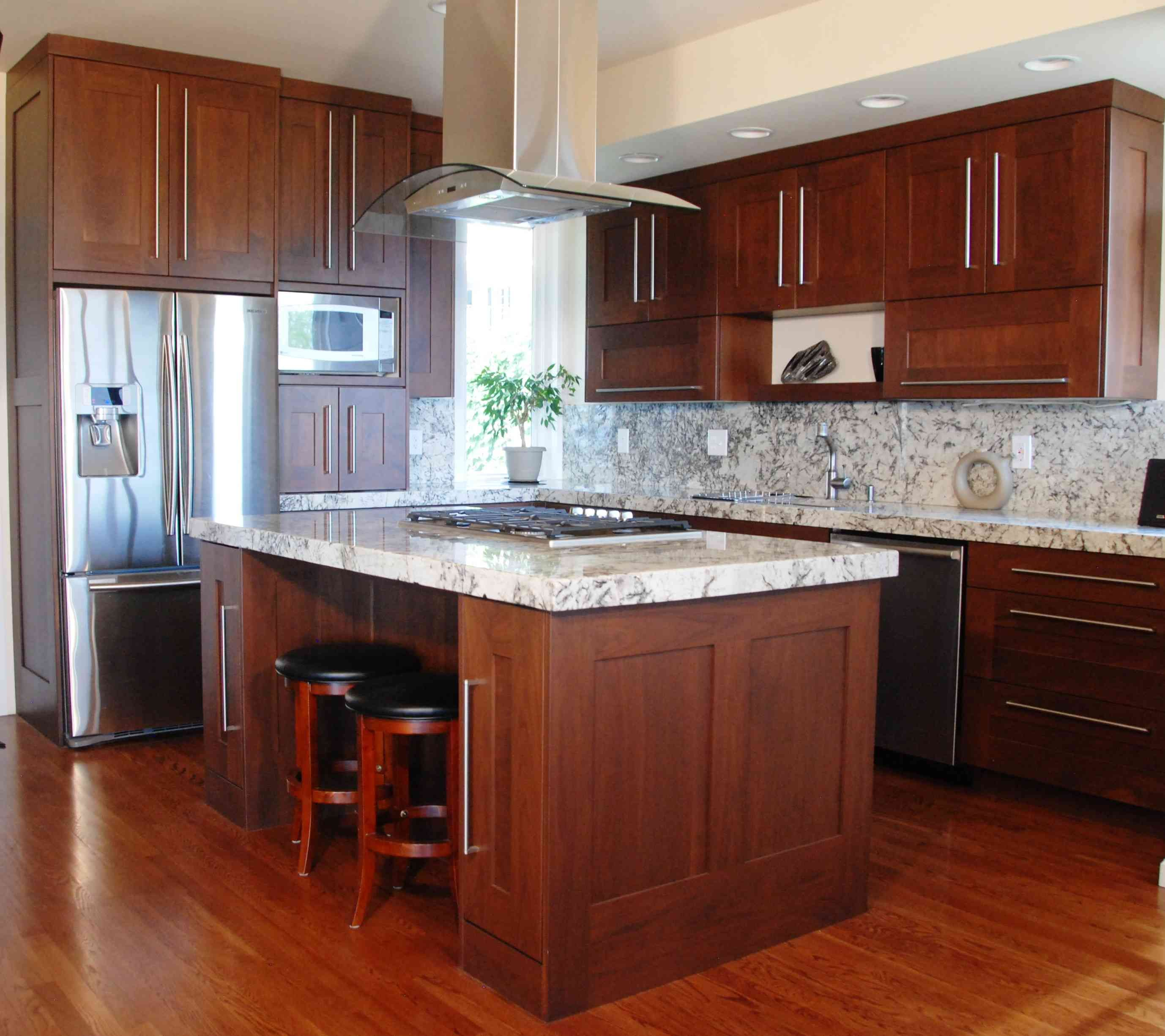 cherry wood cabinets with white granite counters and white island
