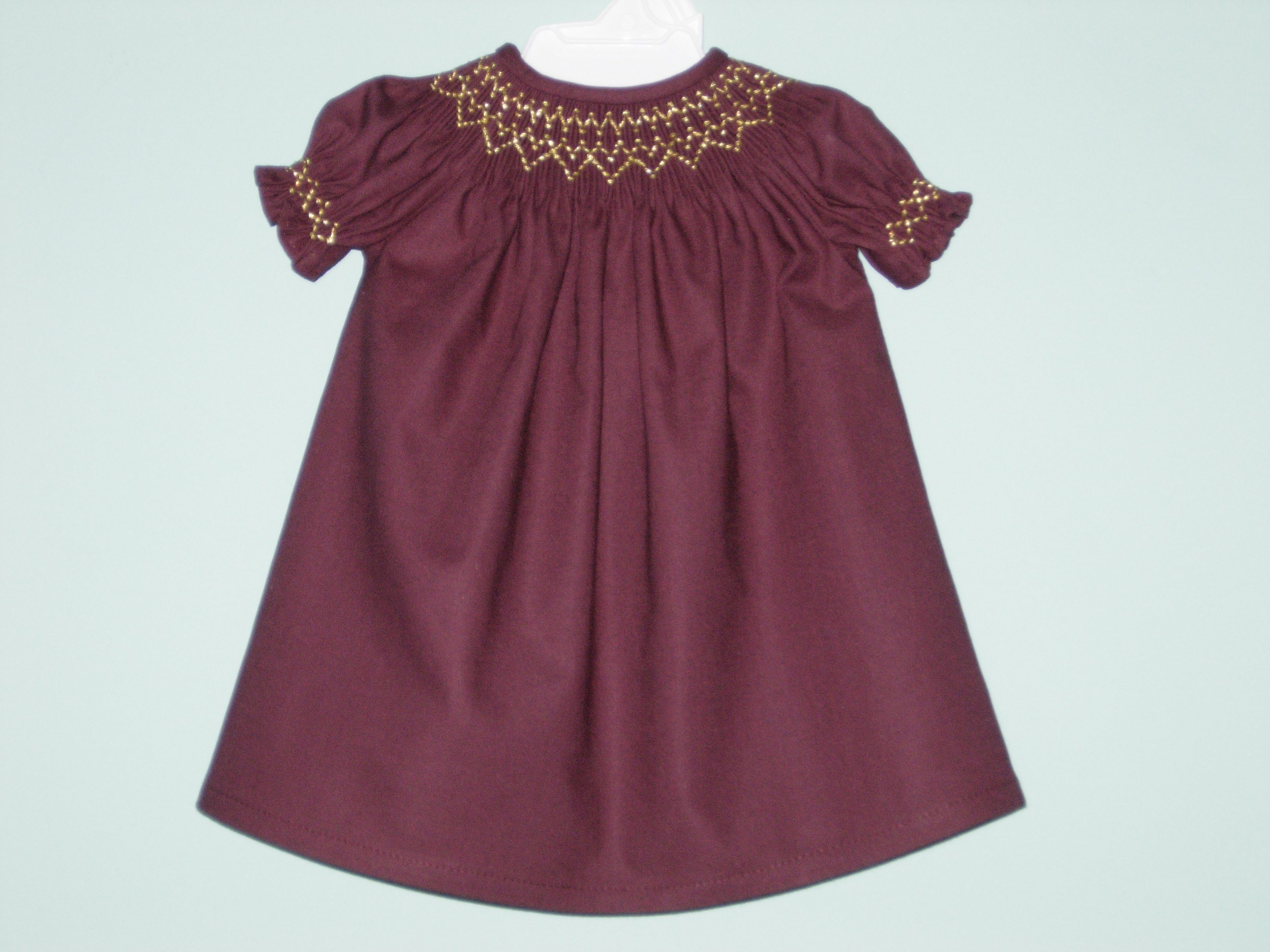 Gold metallic smocking decorates the neckline and sleeves of this hand smocked bishop dress for American Girl dolls.