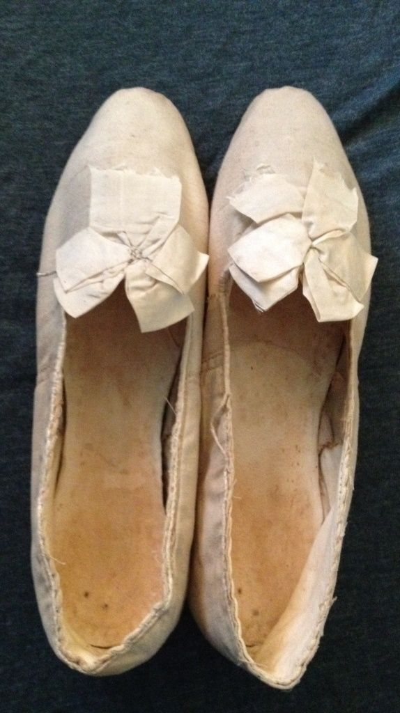 1810-1830 cream toile shoes with ribbon rosette. Straight soles. No back seam. Inner linen.