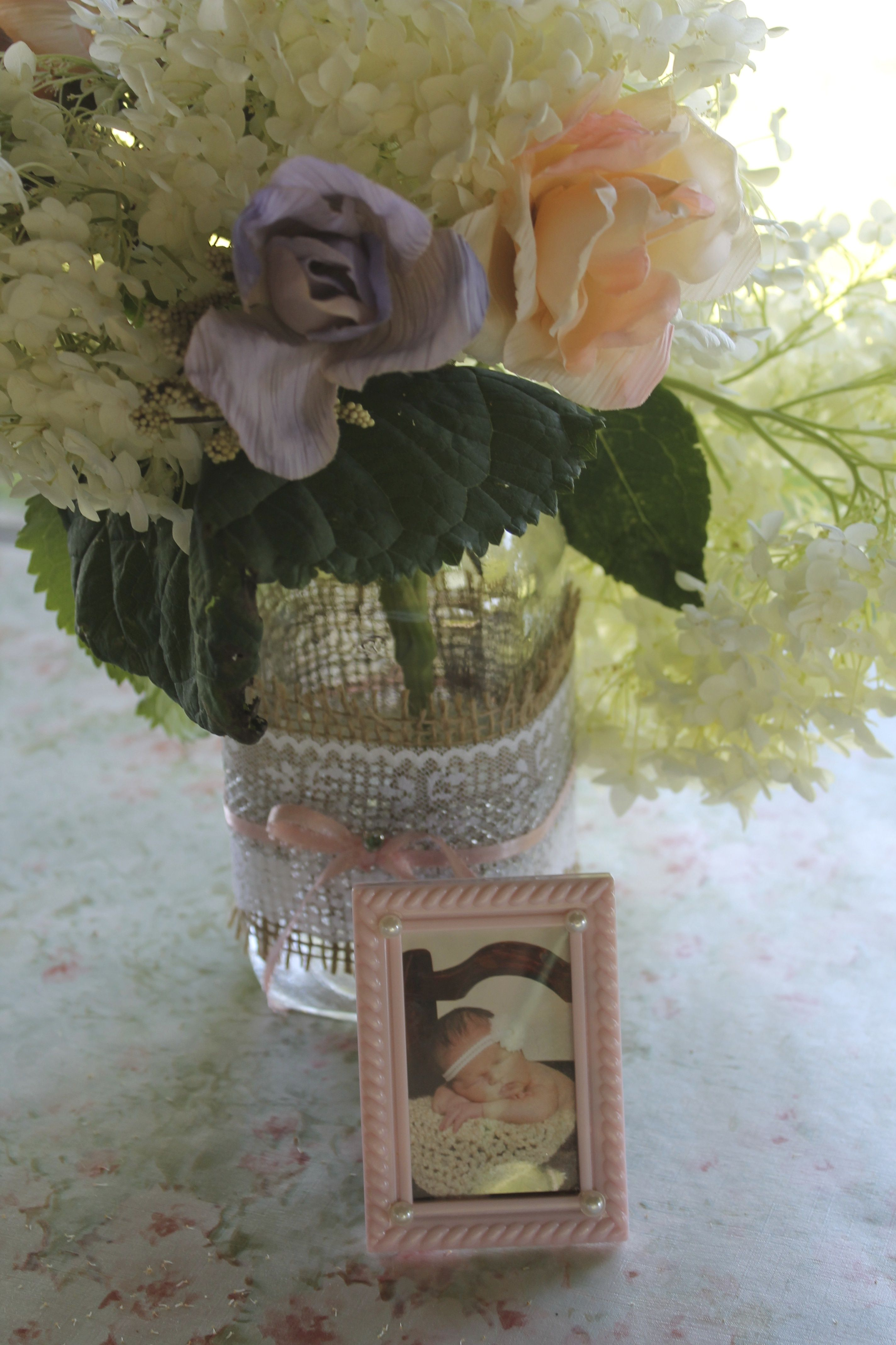 DIY table center piece.  Decorated mason jar, with flowers.  photo frames of Haley and Alex together and growing up.