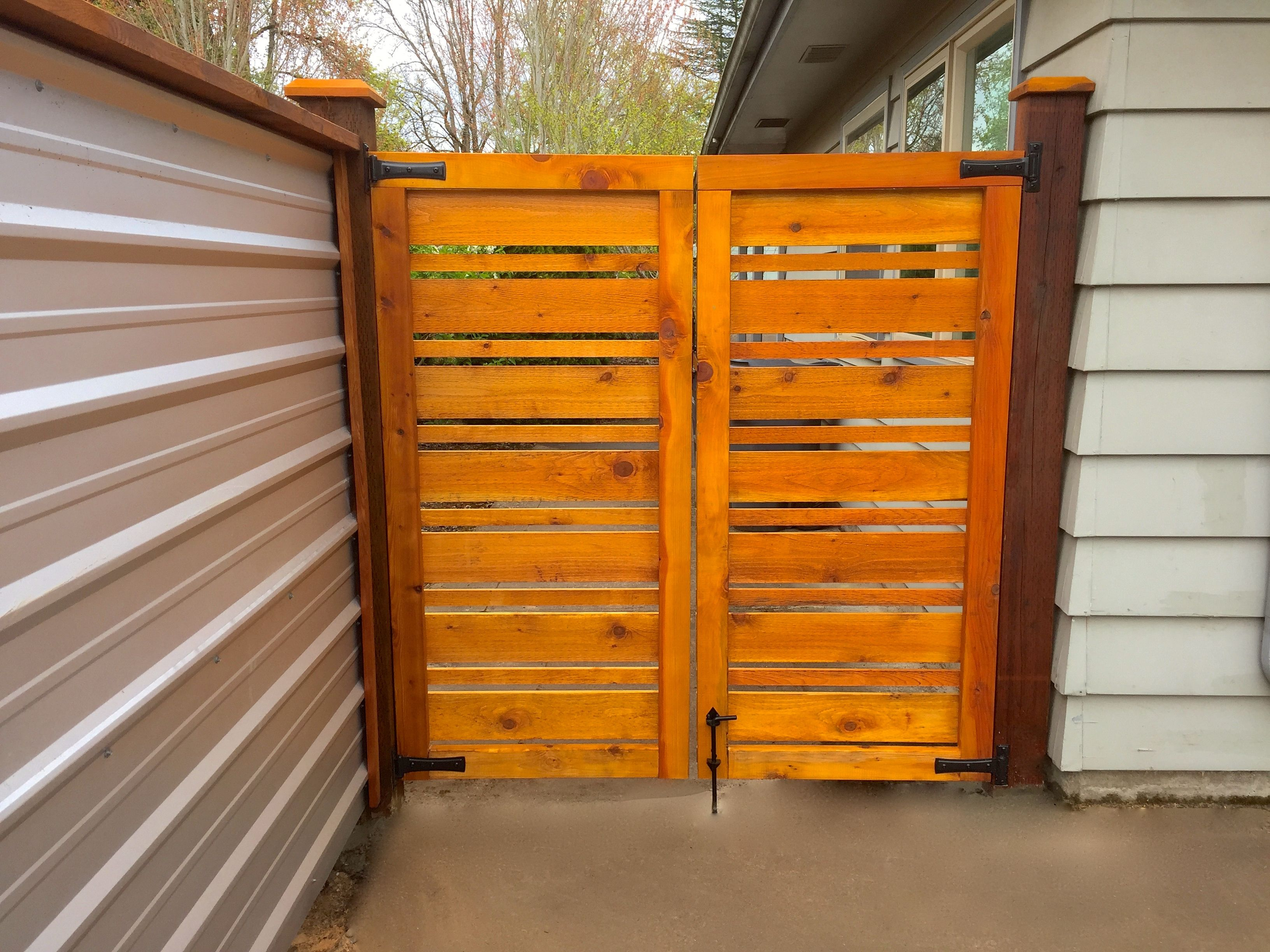 A galvanized corrugated metal fence and cedar gate reflect for Horizontal wood siding panels