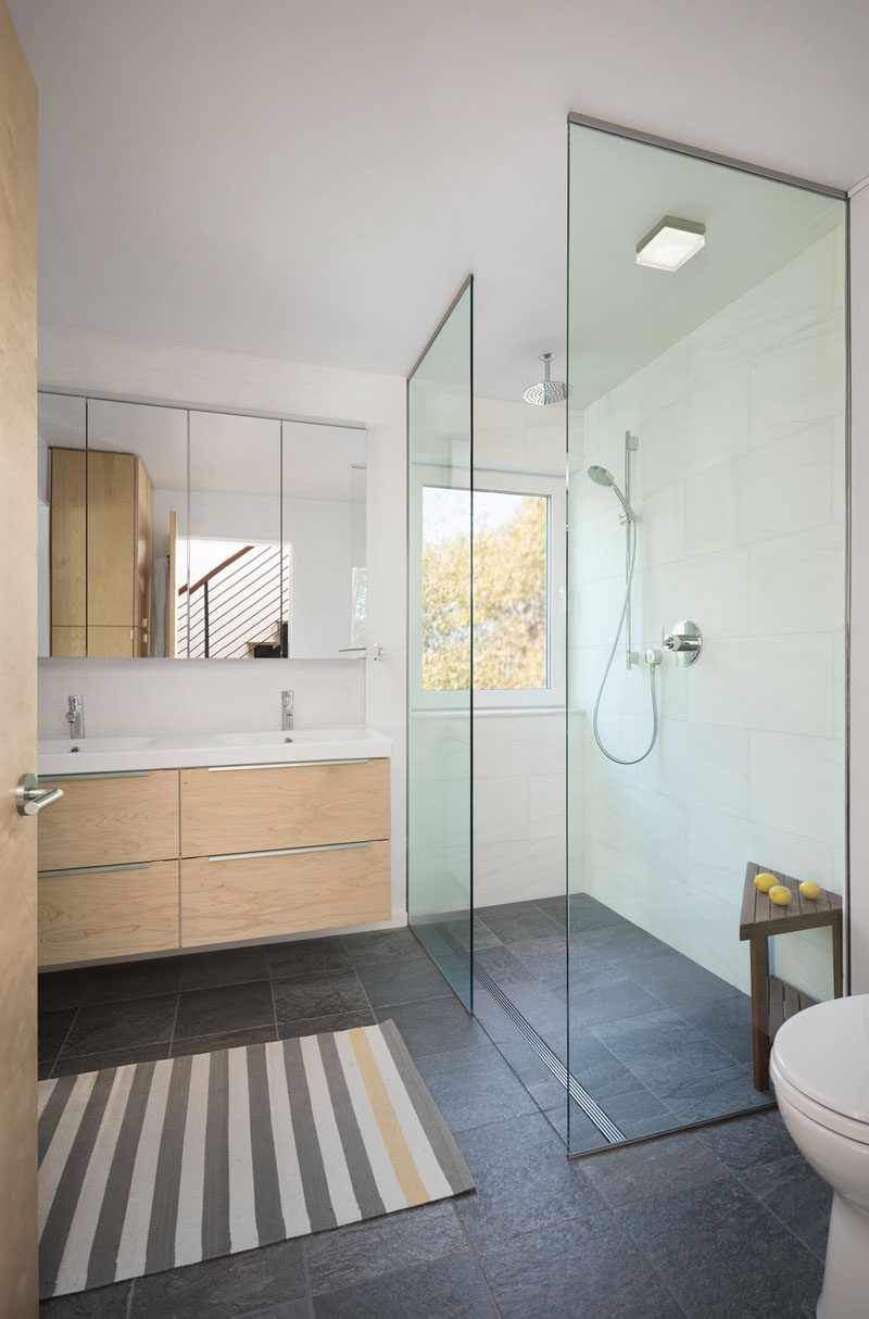 This contemporary bathroom has a glass shower stall with a rain shower head and a window for looking at the trees while showering