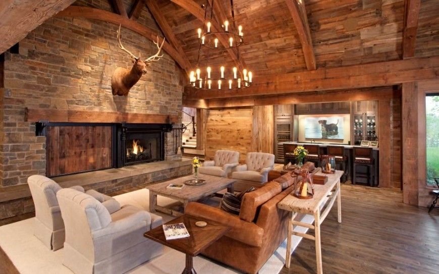 Another view of the above living room, featuring the enormous stone enclosed fireplace with a sliding door to cover the fireplace when not in use. An elk's head trophy rests above the fireplace on the large stone wall. To the right is a large wet bar.