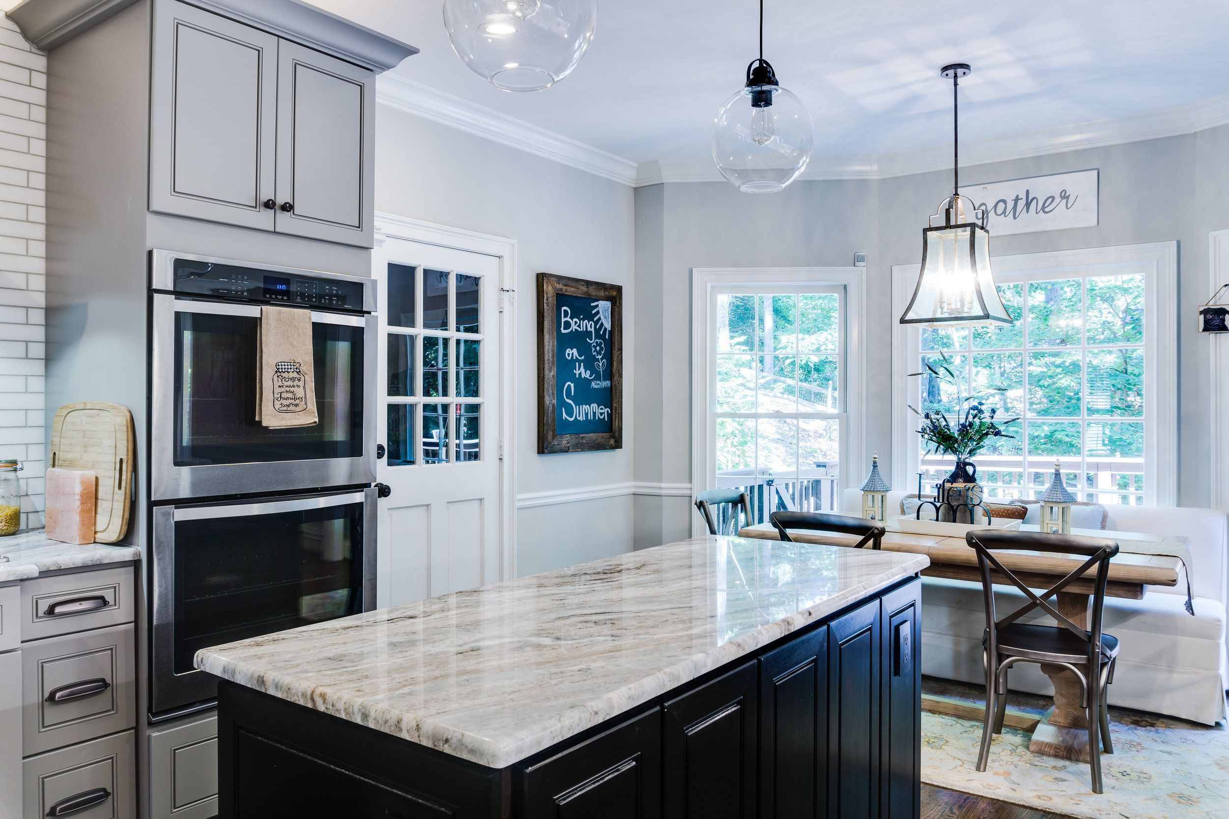 Transitional kitchen with grey cabinets and dark island. Subway tile ...