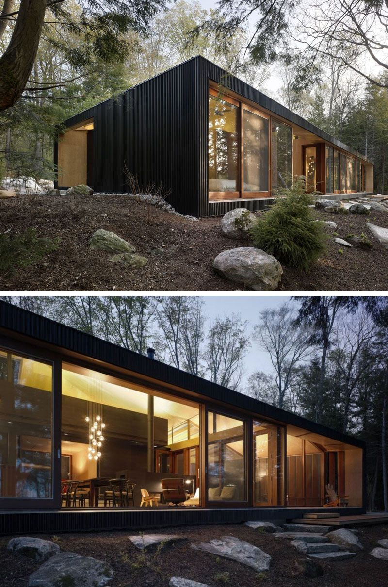 The only parts of this modern home not covered in black siding are the floor to ceiling windows and doorways.