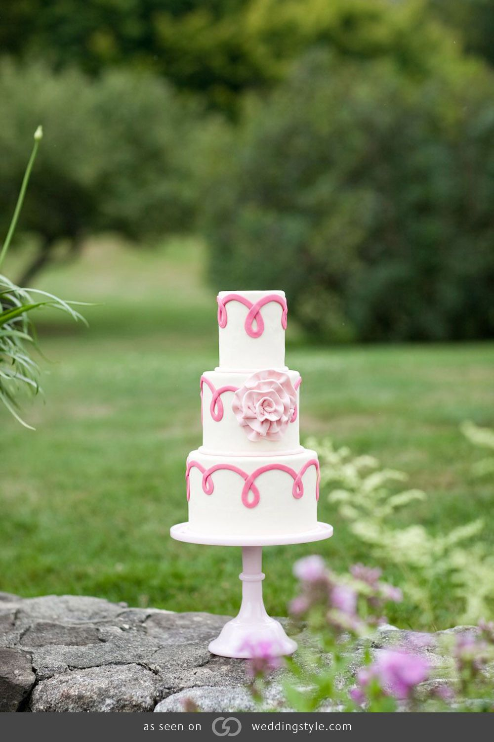 Three-tiered ivory fondant cake with pink fondant ribbon and a light pink ruffled flower.