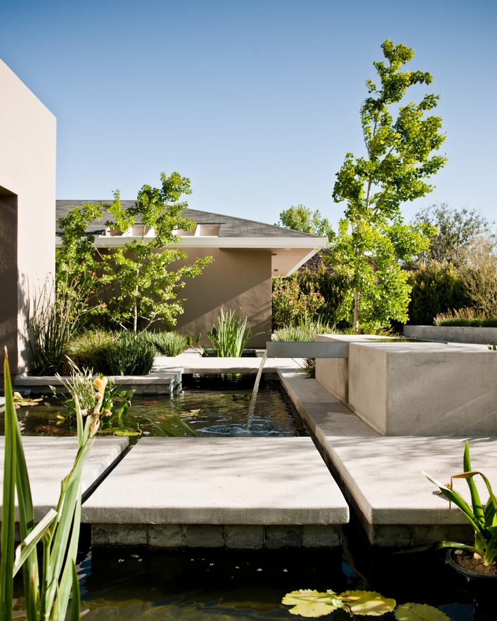 Modern desert garden with waterfall pool and dining space