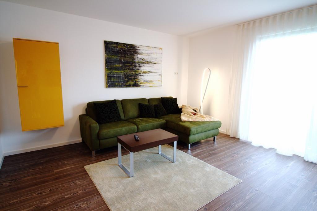 Wohnzimmer mit dunkelgrüner Couch, Kunstdrucken und