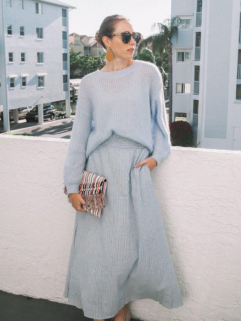 Monochromatic blue look featuring H&M sweater, Agnes & Dora Woven Ball Skirt, Stella & Dot clutch, Nickel + Suede earrings topped off with Karen Walker sunnies.  #stellaanddot #chambrayskirt #beachstyle