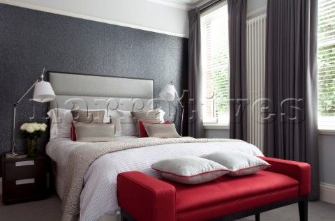 Muted grey bedroom with red footstool and matching anglepoise bedside lamps  in contemporary London h. Muted grey bedroom with red footstool and matching anglepoise