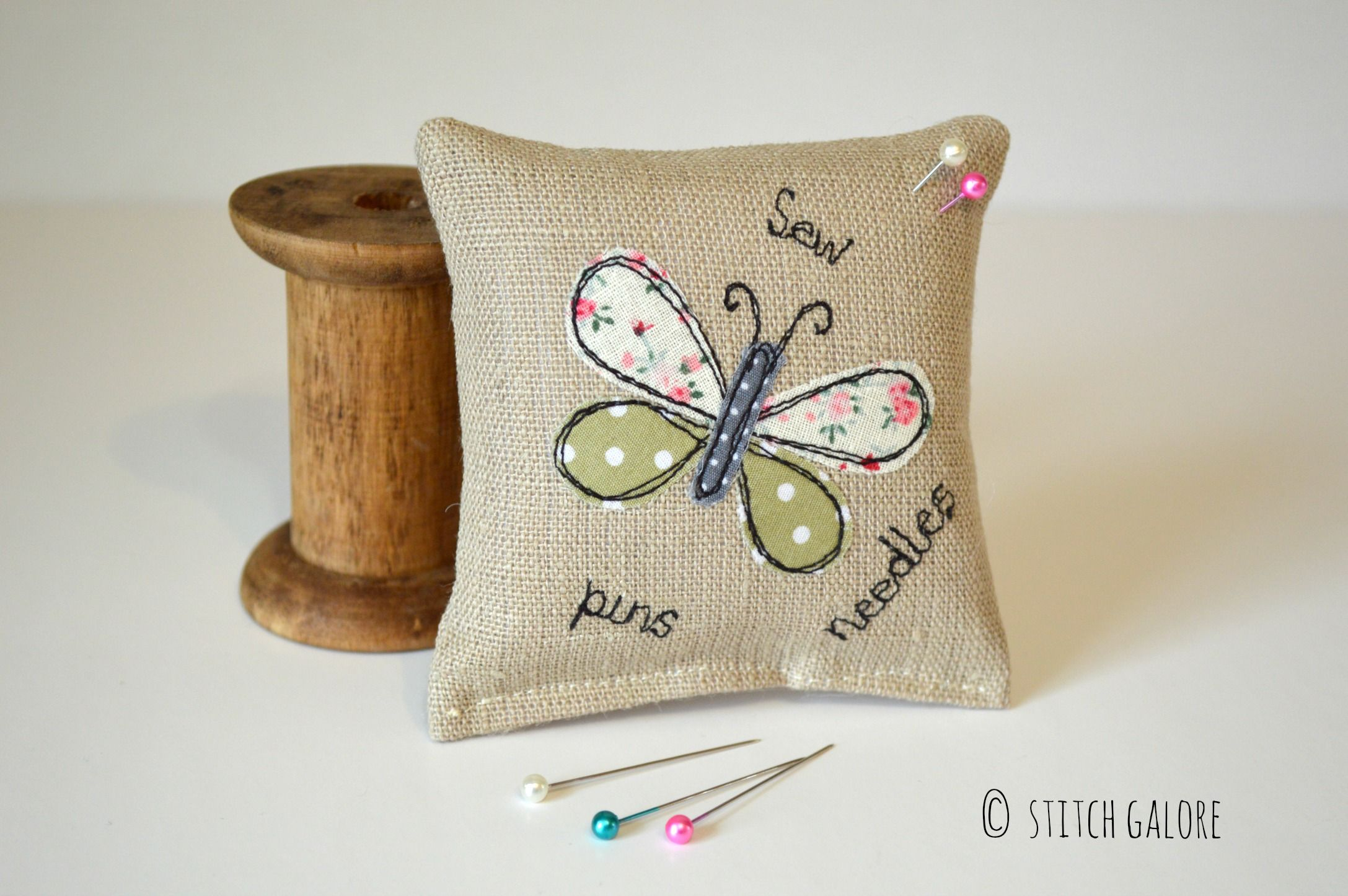 Pincushion made from linen fabric decorated with a green applique butterfly and the words sew, pins and needles handmade by Stitch Galore. www.stitchgalore.com