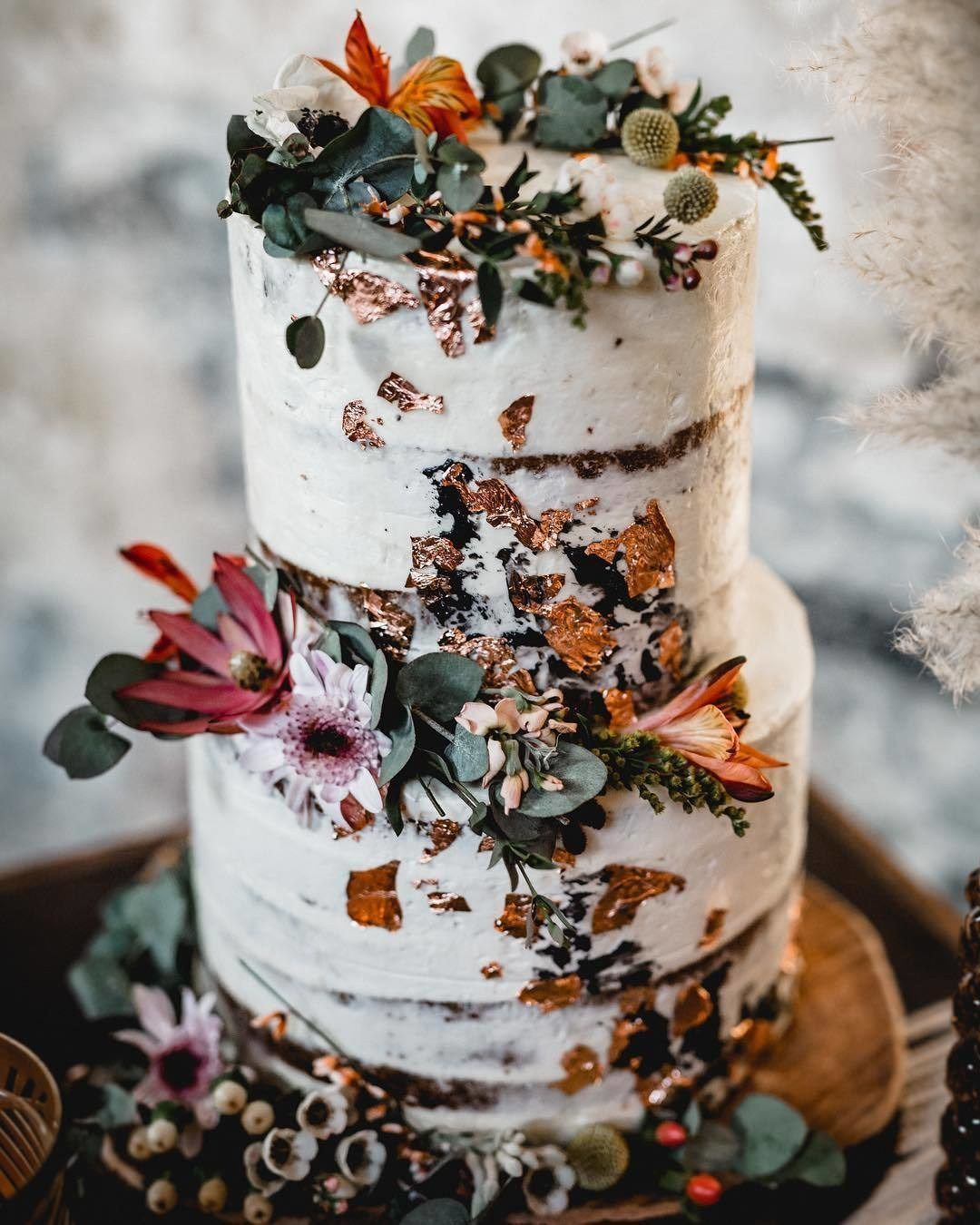 Semi naked wedding cake with rosé gold leaf and black buttercream decorated with eucalyptus and flowers wedding cake #weddingcake #cake